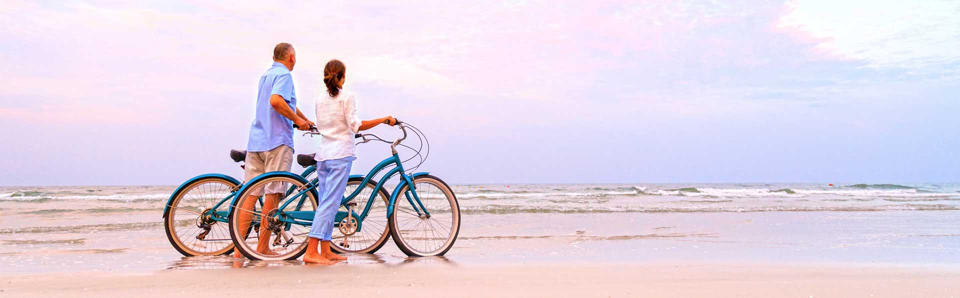 Seniors riding bicycles on the beach