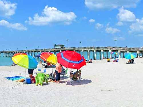 colorful beach umbrellas in front of the venice fishing pier